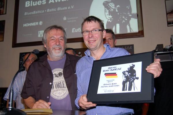Horst-Dieter Fischer (l.), 1. Vorsitzender des ausrichtenden ?Baltic Blues e.V.?, überreichte den ?Blues Award? an Richard Hölscher. Foto: (D. Hanisch)